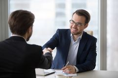 Smiling manager handshaking client applicant at meeting or job interview. Smiling hr manager advisor insurer bank executive handshaking client applicant at stock images