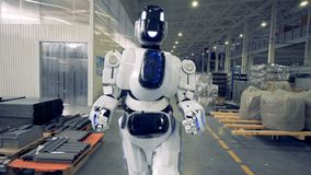Smiling human-like robot is walking forwards along the factory facility. 4K stock video footage