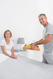 Smiling husband bringing breakfast in bed to wife Royalty Free Stock Images