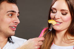 Smiling husband feeding happy wife with apple. Royalty Free Stock Photos