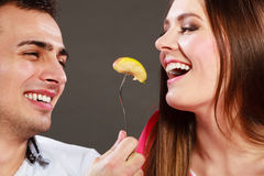 Smiling husband feeding happy wife with apple. Royalty Free Stock Photography
