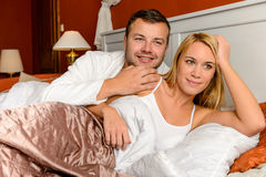 Smiling husband holding wife lying bed married Stock Photography