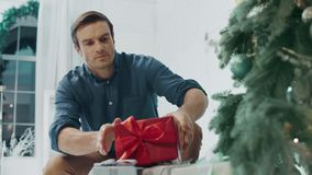 Smiling husband making surprise on christmas eve in living room stock video