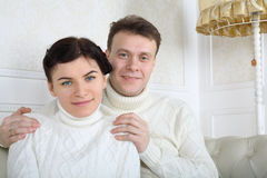 Smiling husband in white sweaters hugs wife shoulders Stock Image