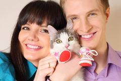 Smiling husband and wife hold cat Stock Image