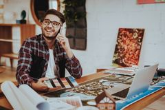 Smiling Illustrator Talking Phone Work on Project. Portrait of Young Bearded Hipster Guy Sits at Workplace Using Laptop, Smartphone Holds Color Palette stock images