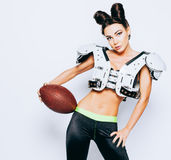 Smiling incredibly beautiful, athletic brunette girl in a shoulderpads and an American football helmet demonstrating royalty free stock photo