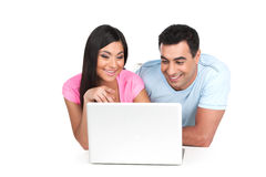 Smiling Indian couple looking together at laptop. Royalty Free Stock Photography