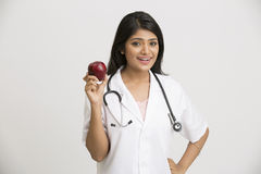 Smiling Indian female doctor holding red apple Royalty Free Stock Images