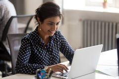 Smiling Indian female employee using laptop at workplace. Looking at screen, focused businesswoman preparing economic report, working online project, cheerful royalty free stock photos