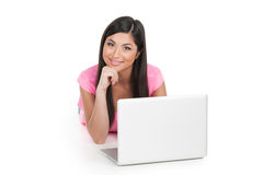 Smiling Indian girl laying with laptop. Stock Photo