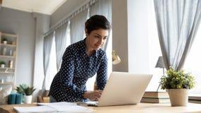 Free Smiling Indian Girl Standing At Desk, Working On Laptop Royalty Free Stock Image - 176482776