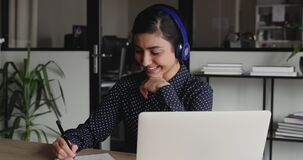 Smiling indian girl wearing headphones looking at laptop making notes