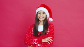 Smiling indian kid girl wear santa hat stand on red background, portrait.