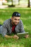 Indian Man Taking Rest at Park. Smiling Indian man lying on green lawn and posing for photography while surfing Internet on modern digital tablet, portrait shot Royalty Free Stock Photography
