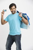 Smiling Indian man showing with credit card with shopping bag Royalty Free Stock Images