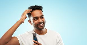 Smiling indian man with trimmer touching his hair. Grooming and people concept - smiling young indian man with trimmer touching his hair over blue background royalty free stock image
