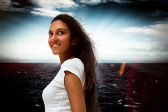 Smiling Indian woman against a dark dramatic sea Stock Photos