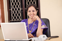 Smiling Indian woman at work Stock Photo