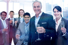 Smiling inernational business team holding glasses of Chamoagne stock photos