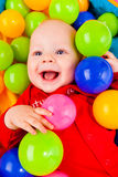 Smiling infant. Portrait of a smiling infant lying with colorful balls Royalty Free Stock Photo