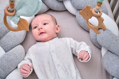 Smiling infant baby boy playing with a wooden mobile suspended above the crib. Happy child playing in bed with toys