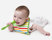 Smiling infant baby with spoon in mouth. Smiling infant baby girl with spoon in mouth Royalty Free Stock Photography