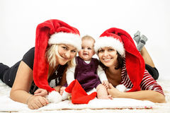 Smiling infant baby with two womans with santa hats. Smiling infant baby with mother and her aunt with santa hats Stock Photo