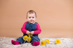 Smiling infant baby with yellow flowers. The first year of the new life Stock Photography