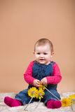 Smiling infant baby with yellow flowers. The first year of the new life Royalty Free Stock Image