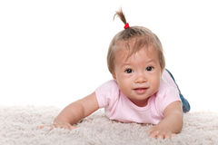 Smiling infant girl on the white carpet Royalty Free Stock Photos