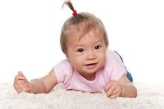 Smiling infant girl on the white carpet Stock Images