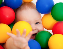 Smiling infant lying among colorful balls. Portrait of a smiling baby lying among colorful balls Royalty Free Stock Photos