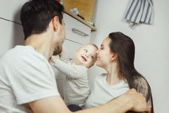 Smiling infant stands holding hand on chest of drawers. Trying to support himself from fall, his parents looking at him, warm relationships, togetherness Stock Photo