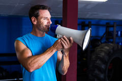 Smiling instructor holding megaphone. In gym Stock Photo