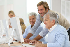 Smiling instructor with seniors in class training Royalty Free Stock Image