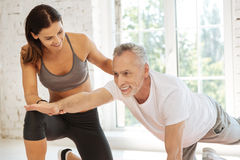 Smiling instructor supporting her client. Good support. Delighted mature bearded male person expressing positivity while doing exercises and raising right arm Stock Images