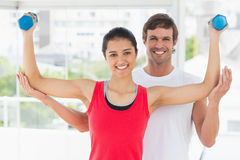 Smiling instructor with woman lifting dumbbell weights. Portrait of a smiling instructor with women lifting dumbbell weights in a bright gym Stock Images