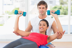 Smiling instructor with woman lifting dumbbell weights. Portrait of a smiling instructor with women lifting dumbbell weights in a bright gym Stock Photography