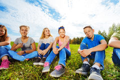 Smiling international friends sitting together. On grass in park during sunny autumn day Stock Image