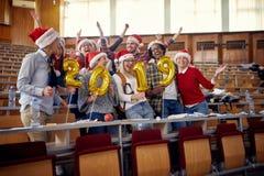 Smiling international students in Santa hat celebrating holiday royalty free stock photo
