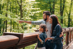 Smiling interracial family standing on wooden bridge, while father pointing somewhere into the forest. Young smiling interracial family standing on wooden bridge Royalty Free Stock Images