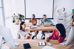 Smiling interracial young business people talking during work. In office royalty free stock photography