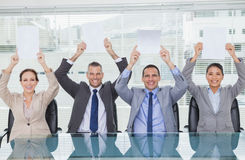 Smiling interview panel holding blank sheets above their head hi Royalty Free Stock Image