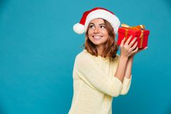 Smiling intrigued woman in sweater and christmas hat holding gift. Box and looking away over blue background Stock Photo