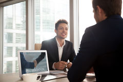 Smiling investment broker showing presentation on laptop screen. Smiling investment broker showing digital presentation on laptop screen to client, friendly royalty free stock photo