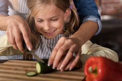 Smiling involved girl cutting a cucumber with her mother Stock Image