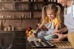 Smiling involved girl helping her mother cooking pastry Royalty Free Stock Photo