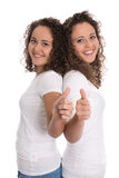 Smiling isolated girls with thumbs up: real twins. Royalty Free Stock Images