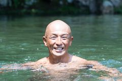 Smiling Japanese bald head guy soaked in water Stock Image